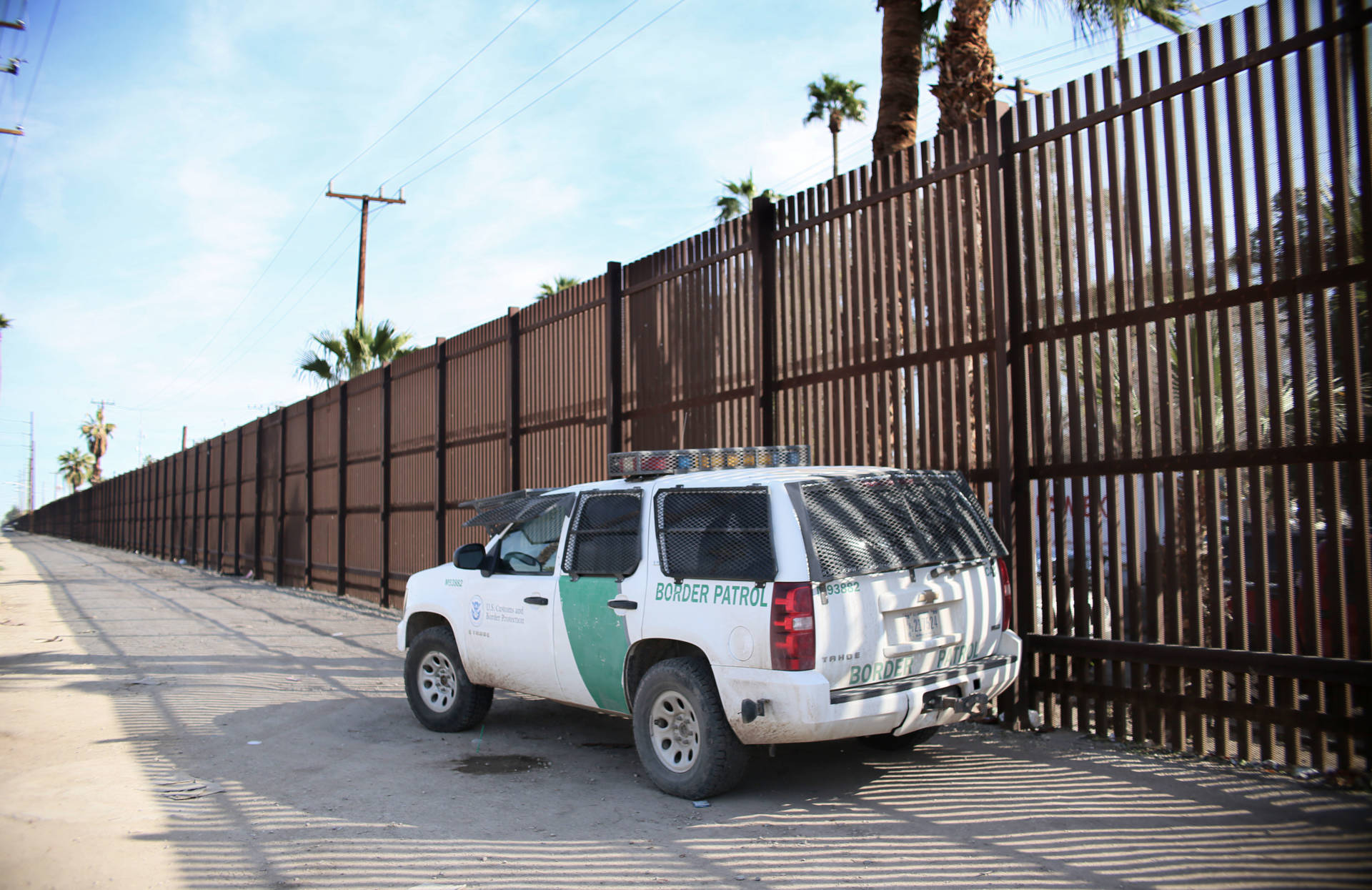 A Border Patrol agent looks over the U.S.-Mexico border wall in Calexico on Jan. 31. Apprehensions at the southern border fell dramatically: from more than 40,000 per month late last year to 18,754 in February, and just 12,193 in March. Sandy Huffaker/AFP/Getty Images