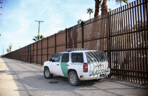 A Border Patrol agent looks over the U.S.-Mexico border wall in Calexico on Jan. 31. Apprehensions at the southern border fell dramatically: from more than 40,000 per month late last year to 18,754 in February, and just 12,193 in March.