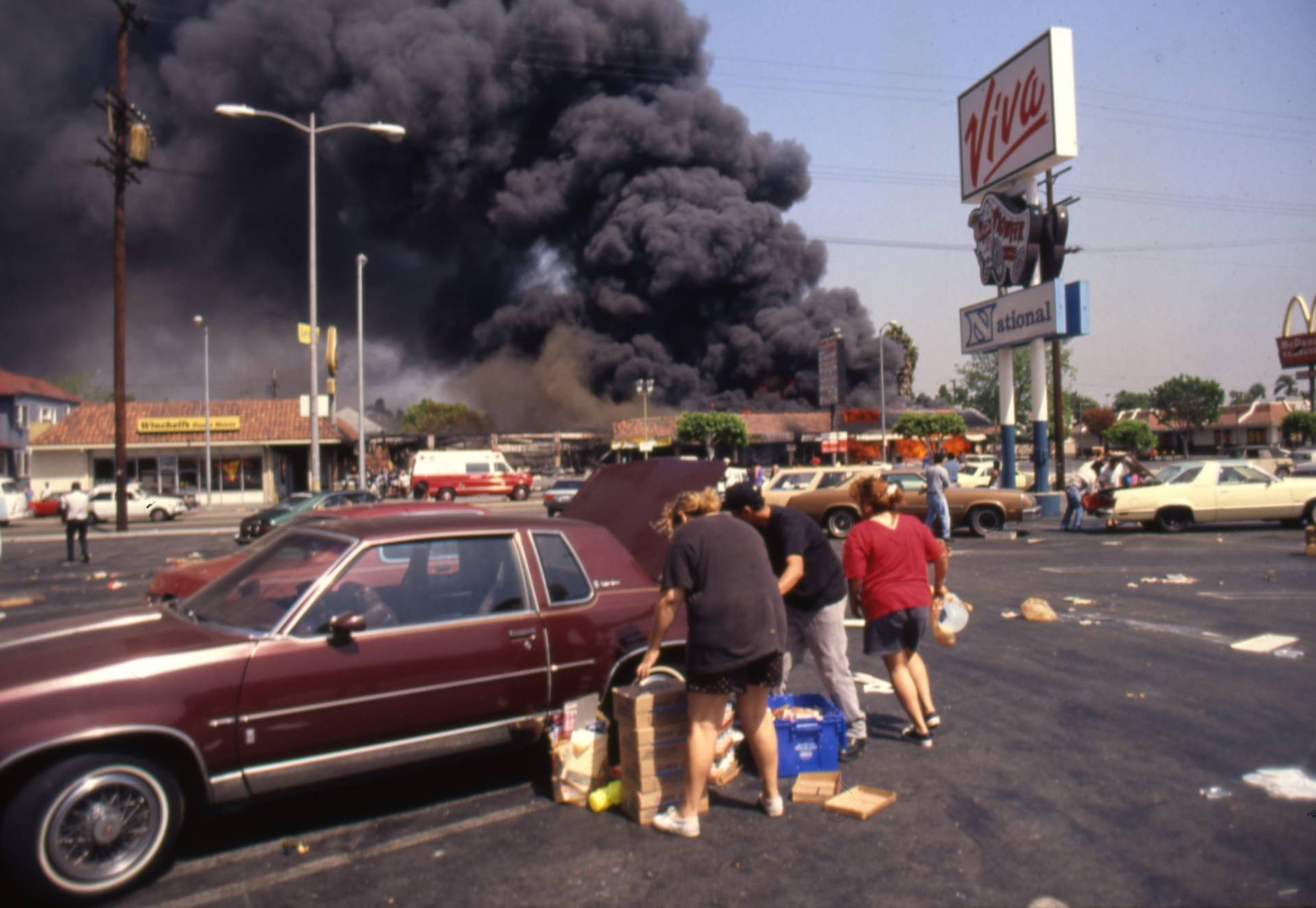 Looters load up a car at the Viva shopping center near a billowing fire during the rioting that erupted in Los Angeles on April 29, 1992, after a jury found four Los Angeles Police Department officers not guilty in the beating of Rodney King. Ron Eisenbeg/Michael Ochs Archives/Getty Images