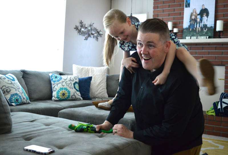 Nick Emery plays around with his oldest daughter Nevaeh, 8, at their Carson City home. She's one of three adopted children in the Emery household.
