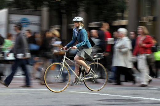 A cyclist rides her bike down Market Street in San Francisco.