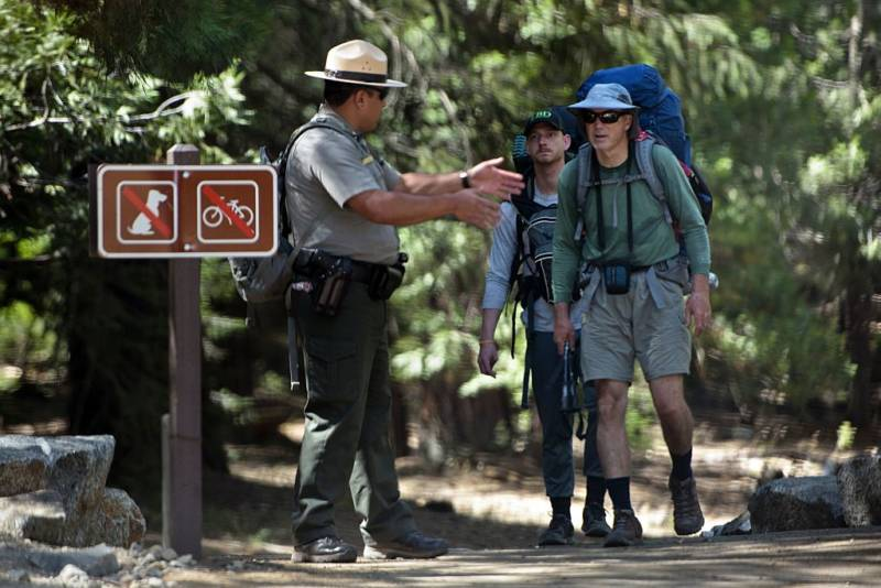 A park ranger directs hikers in Yosemite National Park.