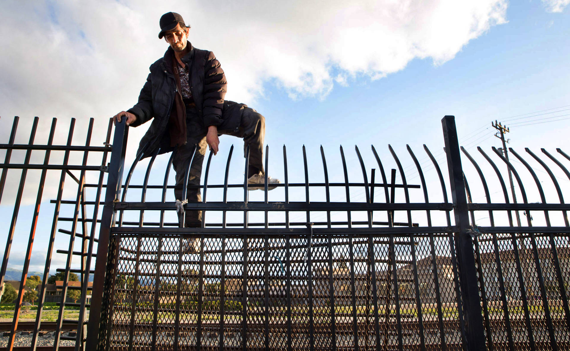 A man climbs over a fence bordering the railroad tracks that separate Chinatown from the rest of downtown Salinas. It's a common route for many Chinatown residents since accessible walking routes in and out of the neighborhood are scarce. Sarah Craig/KQED