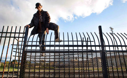 A man climbs over a fence bordering the railroad tracks which separate Chinatown from the rest of downtown Salinas. It's a common route for many Chinatown residents since accessible walking routes in and out of the neighborhood are scarce.