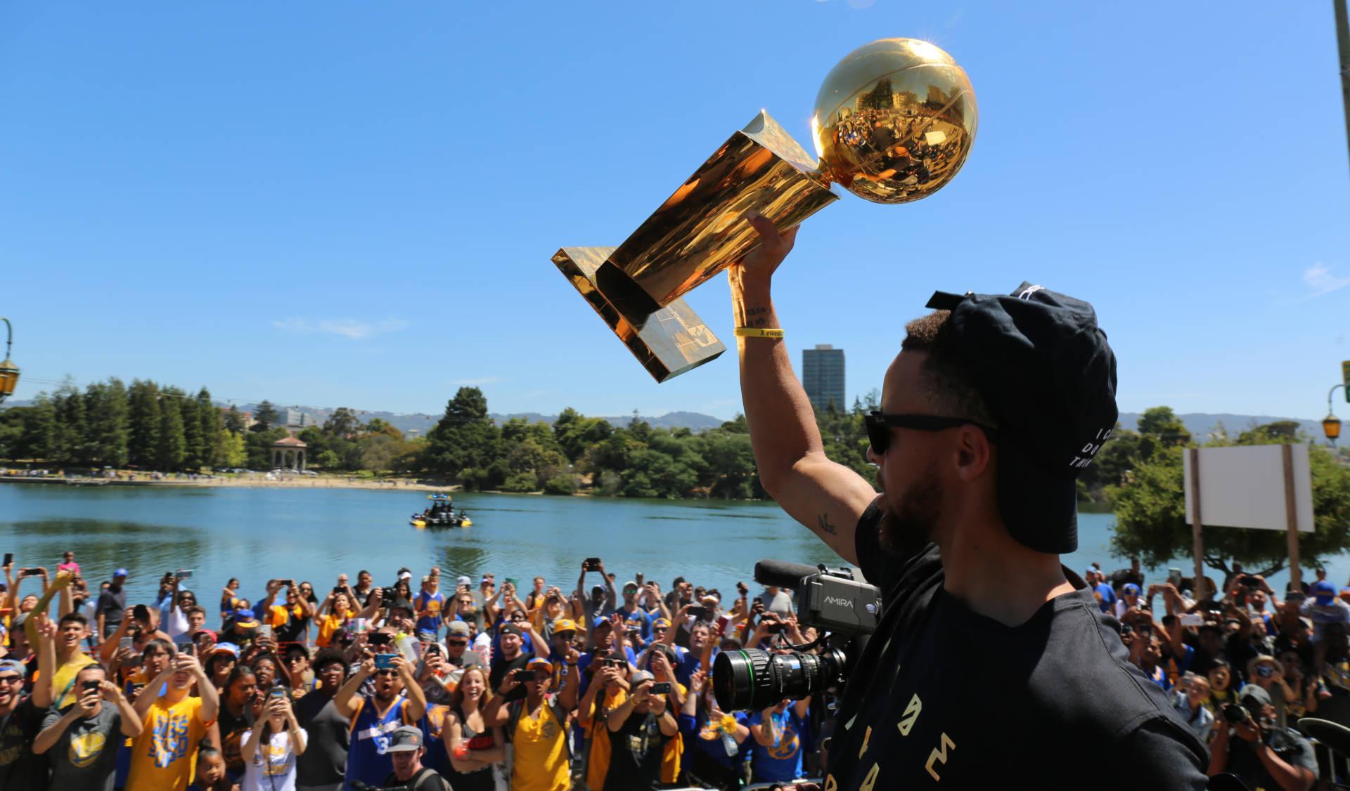 Stephen Curry lifts the NBA Championship trophy to Warriors fans lining Lake Merritt. Adam Grossberg/KQED