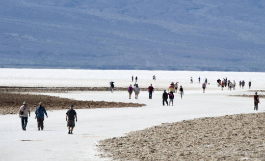 Tourists walk on the salt pan at Badwater Basin in Death Valley National Park.