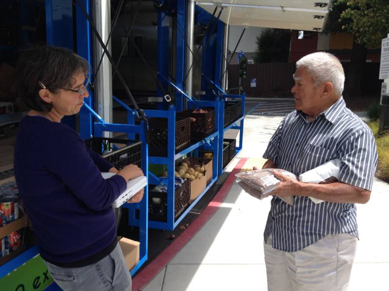 Grocery truck volunteer and recipient Iraneo Garcia chats with Mercy Brown Bag Program Assistant Director Nicole St. Lawrence about how to cook lentils.