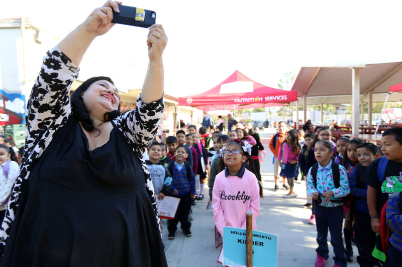 Madison Elementary School Principal Lisa Gonzales-Solomon snaps a selfie with her students one morning before class in Santa Ana. The district is one of 15 CALmatters studied to understand how well the state's new school funding formula is working.