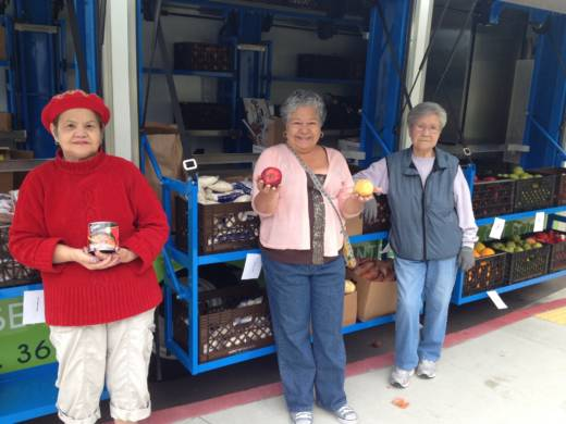 Lilian Mira (center) is ready to serve seniors with other grocery truck volunteers.