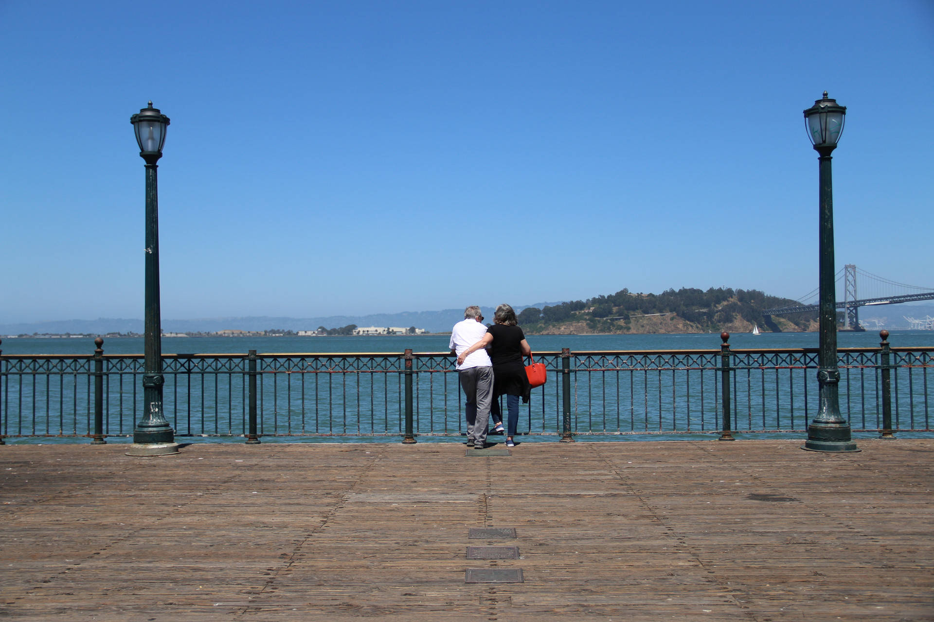 A couple overlooking the San Francisco Bay from Pier 7 on the Embarcadero in San Francisco.  Seginho Roosblad/KQED