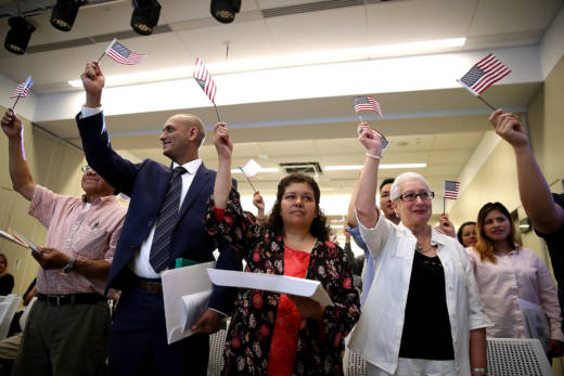 Newly naturalized citizens wave American flags after being sworn in as U.S. citizens during a naturalization ceremony on June 19 in San Francisco.