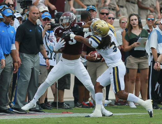 Christian Kirk #3 of the Texas A&M Aggies is forced out of bounds by Randall Goforth #3 of the UCLA Bruins in the first quarter at Kyle Field on September 3, 2016 in College Station, Texas.