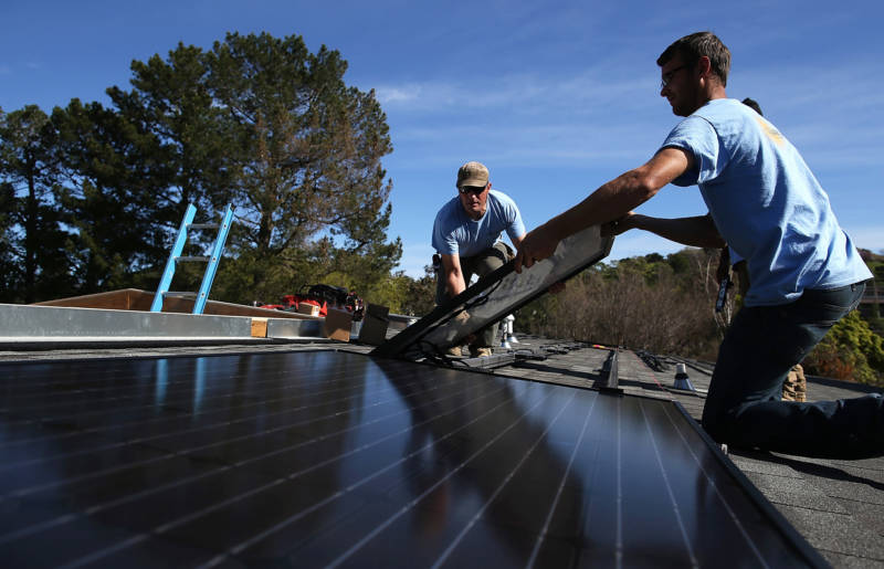 Workers install solar panels on the roof of a home in San Rafael.