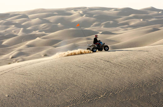 An ATV driver rides in the Colorado Desert at the Imperial Sand Dunes, also known as the Algodones Dunes. Imperial County firefighters and police officers patrol the area, and are partially compensated through the federal PILT program, which President Trump's budget would slash.