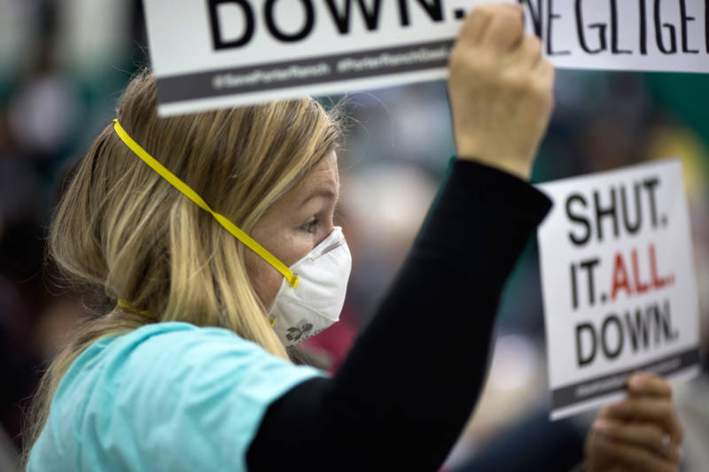 A woman holds a sign at a public hearing before the South Coast Air Quality Management District (AQMD) regarding a proposed abatement order to stop the massive Aliso Canyon natural gas leak, on January 16, 2016, near Porter Ranch.