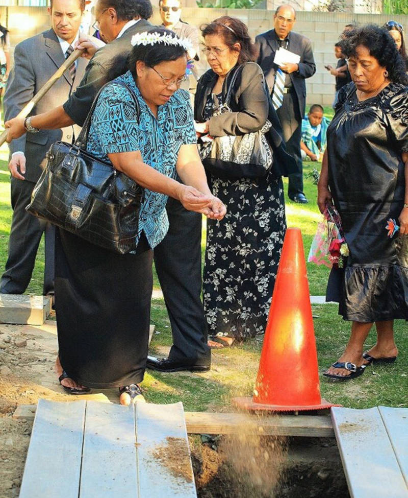 Greta Briand attends a Marshallese funeral and scatters dirt over a grave. Her younger sister, Delta Garstang, far right, is a thyroid cancer survivor.