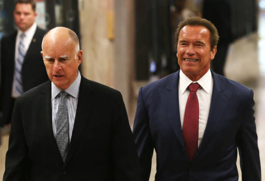 Gov. Jerry Brown and former governor Arnold Schwarzenegger walk in the state Capitol in 2014.