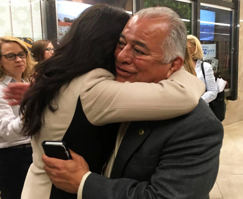 GOP Assemblyman Rocky Chavez gets a congratulatory hug after his vote to back cap-and-trade's reauthorization.