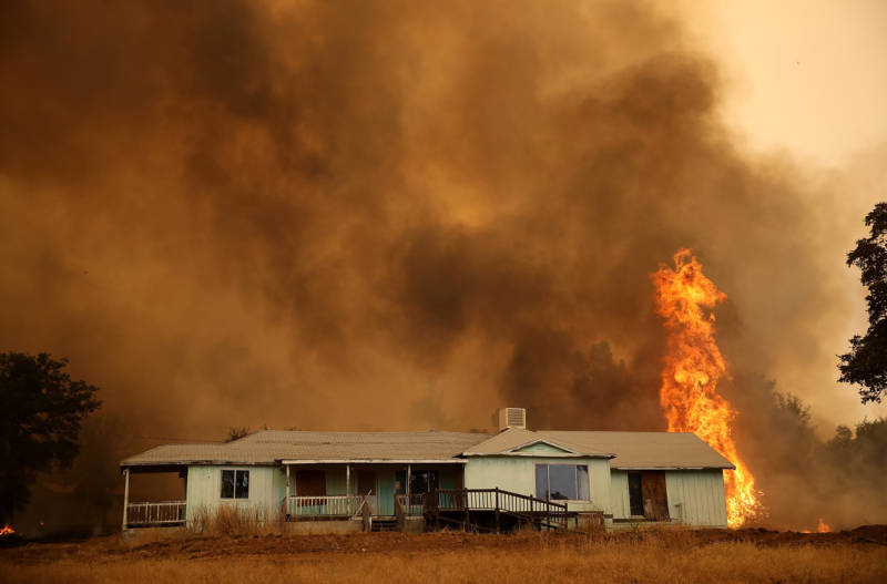 Flames approach a home as the Detwiler Fire burns through brush on July 19, 2017 in Mariposa.
