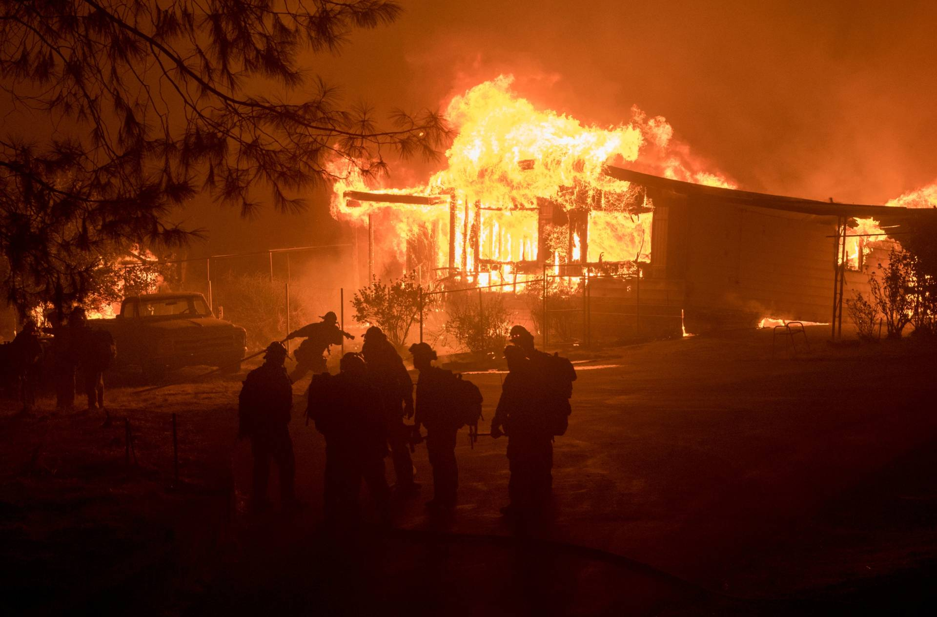 A firefighter carries a hose as a house burns Saturday night east of Oroville. The home was one of 17 structures destroyed by the Wall Fire, which broke out in rural Butte County on Friday. Josh Edelson/AFP-GettyImages