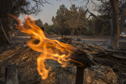 A gas line burns in the ruins of a structure at Rancho Alegre Boy Scouts of America outdoor school that was destroyed by the Whittier Fire on July 9, 2017 near Santa Barbara, California.
