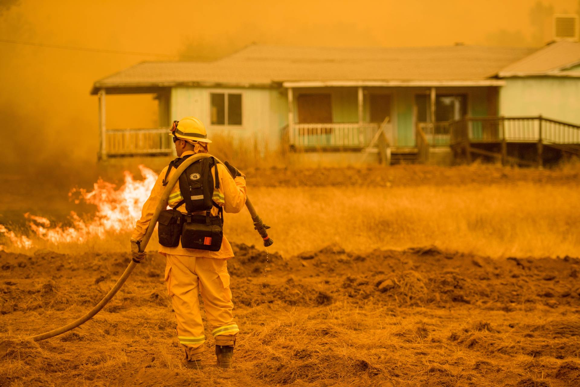 A firefighter works to protect a home in Mariposa, California on July 19, 2017. Josh Edelson/AFP/Getty Images