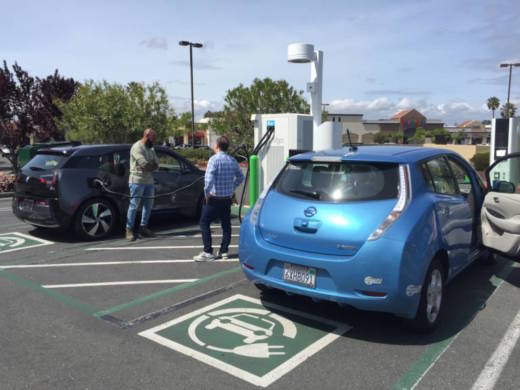 Drivers wait while their electric cars recharge at a charging station in Vallejo.