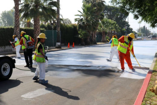 City employees paint a section of Beachy Ave in Pacoima a light gray on June 3, 2017 as part of a pilot project to test out 'cool pavement.'