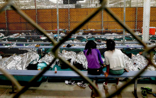 Two young girls sit in a holding area where hundreds of mostly Central American immigrant children were being processed and held at a U.S. Customs and Border Protection facility in 2014.