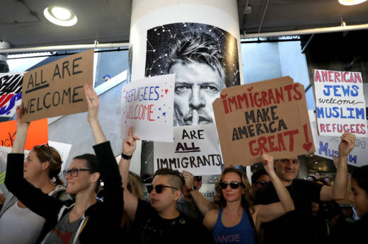 Protesters hold signs during a demonstration against the immigration ban that was imposed by U.S. President Donald Trump at Los Angeles International Airport on January 29, 2017 in Los Angeles, California. Thousands of protesters gathered outside of the Tom Bradley International Terminal at Los Angeles International Airport to denounce the travel ban imposed by President Trump. Protests are taking place at airports across the country.