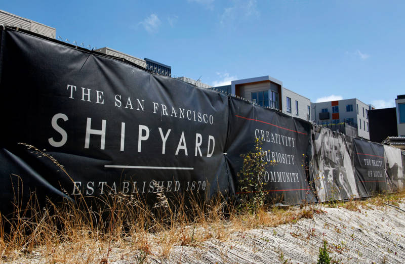 Signs advertising the new Shipyard development surround one of the project's ongoing construction sites at Hunters Point.