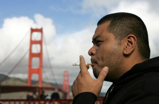 A man smokes a cigarette near the Golden Gate Bridge.