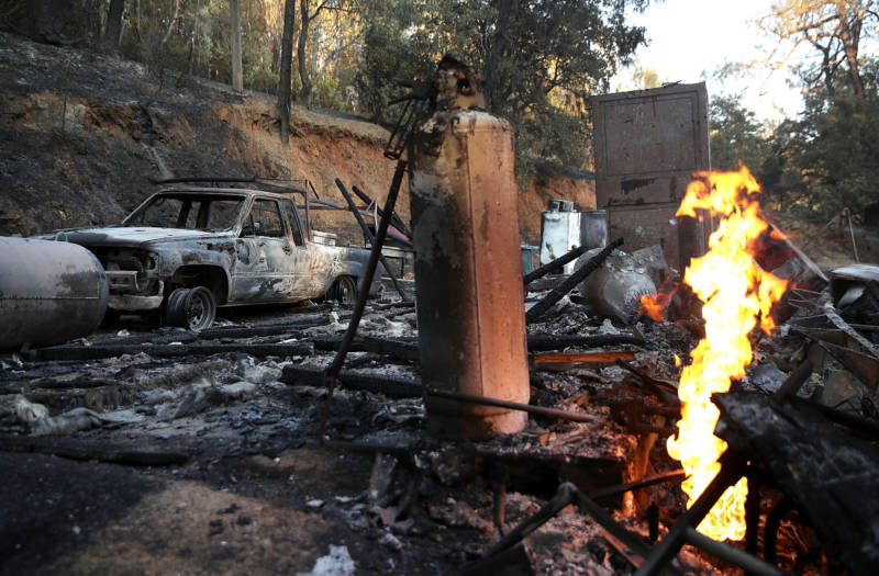 A gas line continues to burn next to a home that was destroyed by the Wall Fire on July 9, 2017 in Oroville.