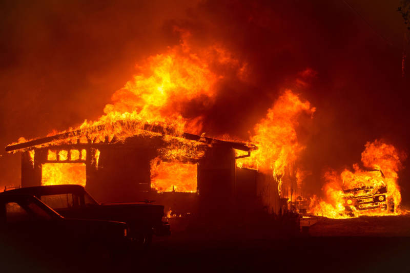 A car and house are engulfed in flames as the Wall Fire burns through a residential area in Oroville on July 8, 2017.