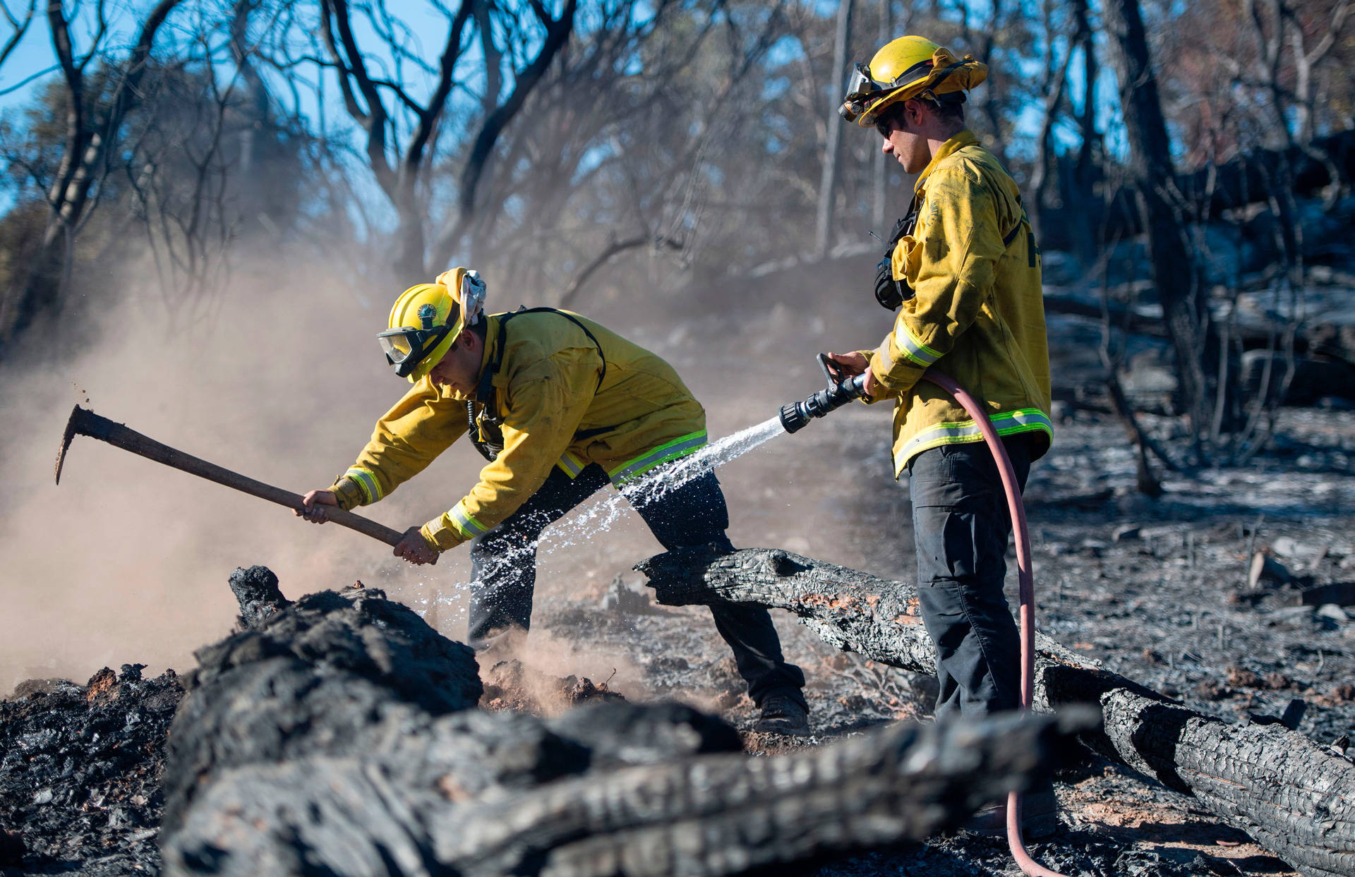 Bryce Briare (R) and Mike Manibusan (L) with the Marin County Fire Deptartment work on a smoldering hot spot as firefighters continue to build toward containment of the Wall Fire in Oroville on July 10, 2017.  JOSH EDELSON/AFP/Getty Images