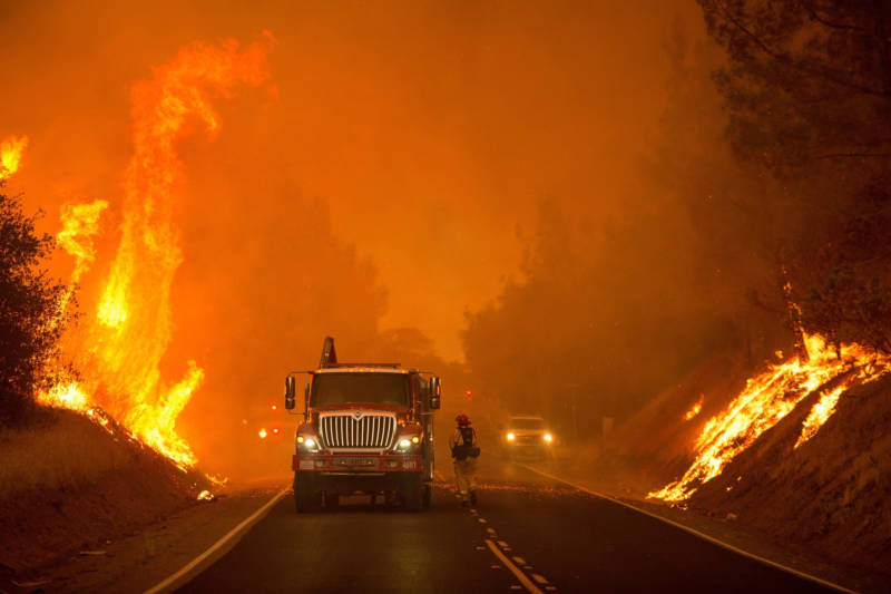 Firefighters scramble to halt the forward progress of the Wall Fire as flames are seen along Forbestown Road in Oroville on July 8, 2017.