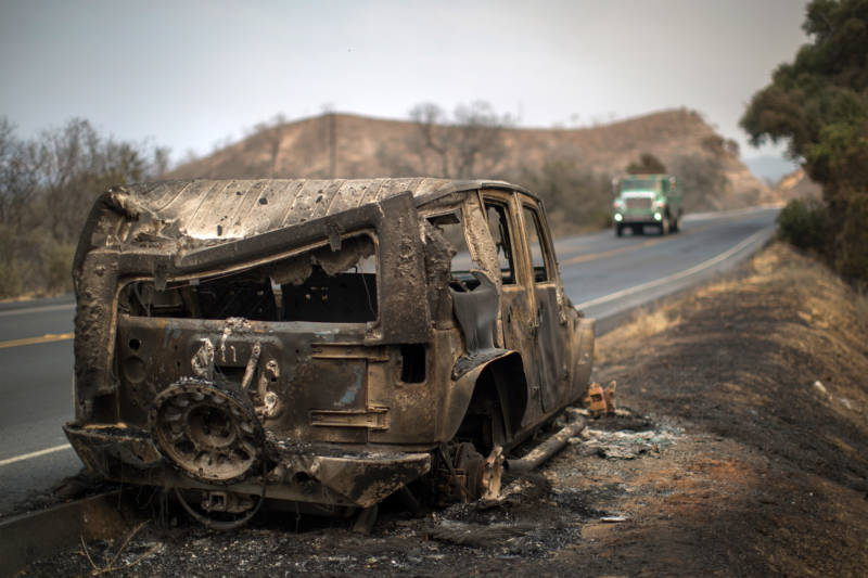 Firefighters pass a car that was destroyed by the Whittier Fire on July 9, 2017 near Santa Barbara