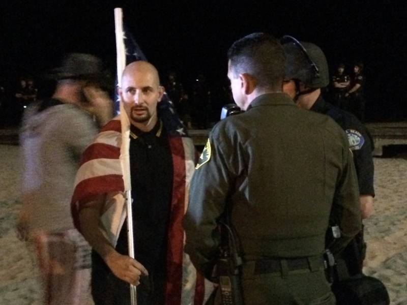 A man who uses the name Johnny Benitez for organizing, but whose legal name is Juan Cavidad, was a rally organizer. He holds an American flag just before he and others with the group America First! were escorted off the beach by police and sheriff's deputies attempting to maintain a physical barrier between America First! demonstrators and the large group of counter-protesters who showed up at Laguna Beach Sunday.