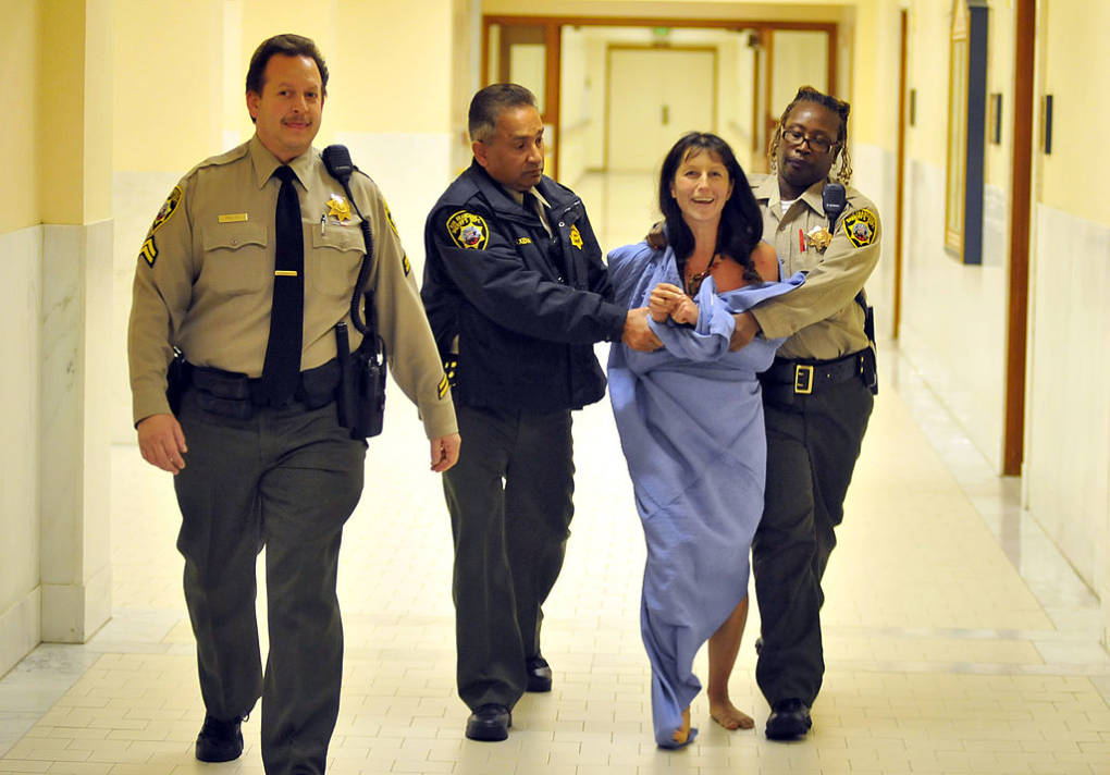 Gypsy Taub who disrobed inside City Hall during a meeting is escorted away on November 20, 2012 in San Francisco.