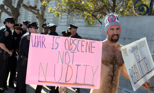 Nude activist Trey Allen stands nude in front of San Francisco police officers as he protests San Francisco's ban on nudity.