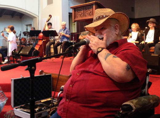 Marine and Navy veteran Kelly Hodell volunteers on harmonica with the 5th Dementia.