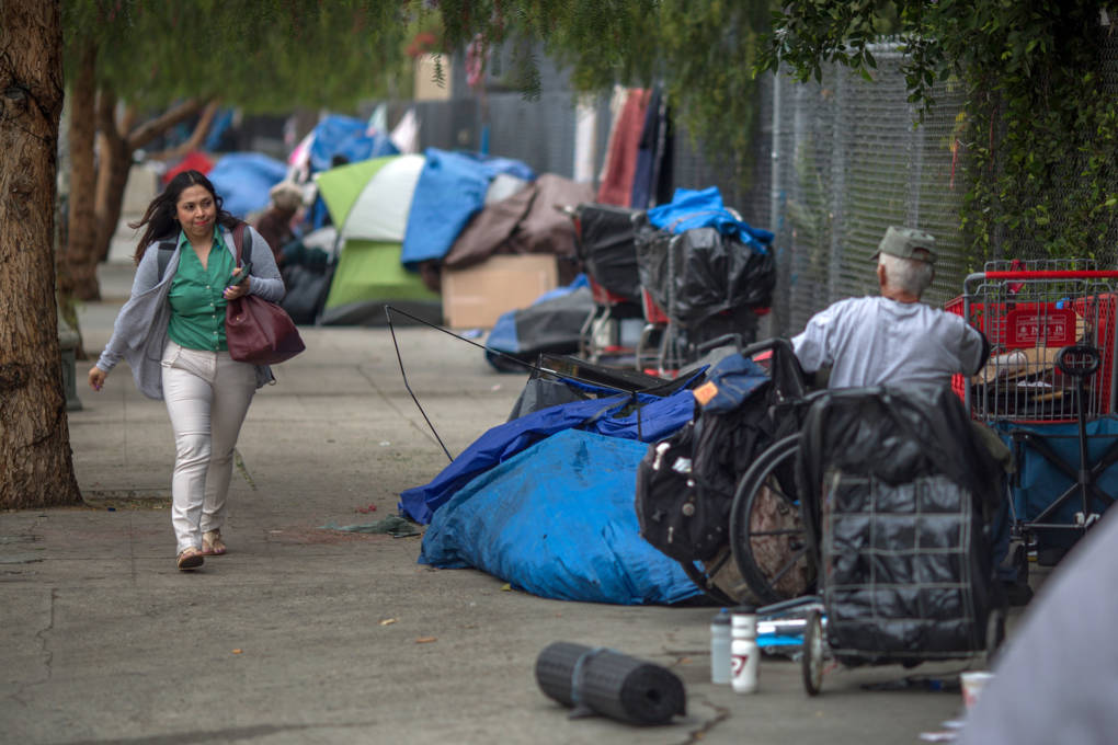 A woman walks past a homeless encampment on May 1, 2017 in Los Angeles.