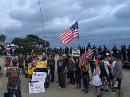 About two dozen people showed up at Laguna Beach Sunday for an America First! rally and vigil they said was in honor of people killed or harmed by immigrants living in the country illegally.