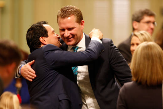 Democratic Assembly Speaker Anthony Rendon (L) embraces former Assembly GOP leader Chad Mayes in December, 2016.