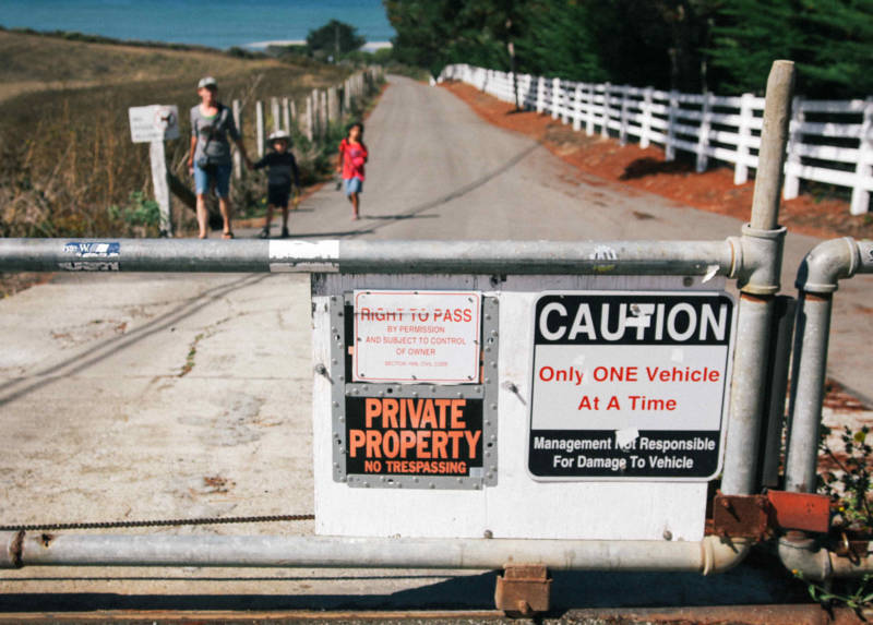 A 'Private Property: No Trespassing' sign on a closed gate leading to Martins Beach.