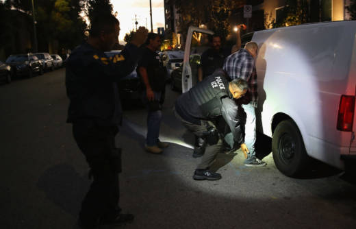 A man is detained by Immigration and Customs Enforcement (ICE), agents early on October 14, 2015 in Los Angeles.