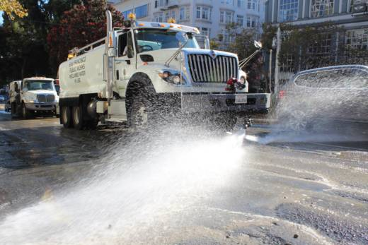 A flusher sprays the streets down with water.