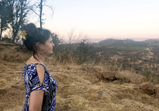 Deb Helleren looks out at the view from her new property. Green vineyards dot the landscape decimated by fire.