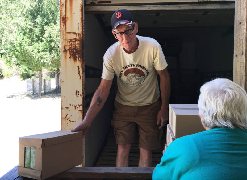 Jeff England unloads boxes at his last stop, Ruth Lake. Site supervisor Sandy Rasche says 45 families come to get food. The local population hovers around 200.
