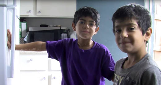 Two young members of the Hamdard family, refugees from Afghanistan, stand in their kitchen. They're one of three large refugee families the IRC helped resettle at an El Cajon apartment complex. The three families are being asked to move because they have too many people living in their homes.